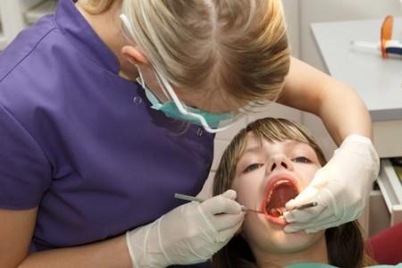Dentista examina criança. Foto: Aigars Reinholds / Shutterstock.com