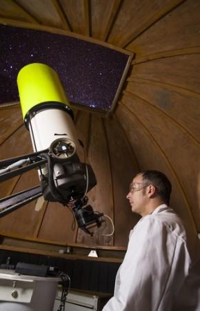 Astrônomo observando corpos celestes com um telescópio. Foto: Henk Stolk / Shutterstock.com